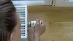 Υψηλή άποψη γωνίας της θερμοστάτη στροφής γυναικών στο θερμαντικό σώμα στο σπίτι απόθεμα βίντεο