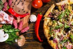 Υψηλή άποψη γωνίας της πίτσας με το arugula και τις ελιές, κοντά στο ψέμα tomat Στοκ εικόνα με δικαίωμα ελεύθερης χρήσης