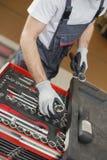 Υψηλή άποψη γωνίας του αρσενικού μηχανικού που τακτοποιεί τα εργαλεία στο συρτάρι στο κατάστημα επισκευής αυτοκινήτων Στοκ Εικόνα