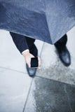 Υψηλή άποψη γωνίας του επιχειρηματία που κρατά μια ομπρέλα και που εξετάζει το τηλέφωνό του στη βροχή Στοκ Εικόνες
