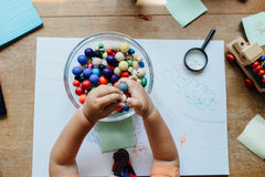 Υψηλή άποψη γωνίας των χαντρών μιας μικρών παιδιών εκμετάλλευσης πέρα από ένα κύπελλο Στοκ φωτογραφίες με δικαίωμα ελεύθερης χρήσης