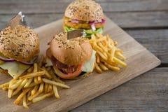 Υψηλή άποψη γωνίας των burgers με τις τηγανιτές πατάτες που εξυπηρετούνται στον τέμνοντα πίνακα Στοκ φωτογραφία με δικαίωμα ελεύθερης χρήσης