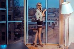 Υψηλή ξανθή γυναίκα κοινωνίας στα γυαλιά με το φλυτζάνι του τσαγιού από το larg Στοκ εικόνα με δικαίωμα ελεύθερης χρήσης
