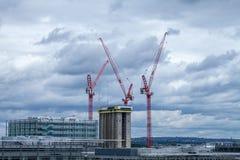 Υψηλή οικοδόμηση κτηρίου ανόδου με τους κόκκινους γερανούς πέρα από το Λονδίνο Στοκ Φωτογραφίες