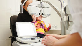 Υψηλή τεχνολογία στην οφθαλμολογία - optometrist στην κλινική που ελέγχει το όραμα μικρών κοριτσιών ` s - ιατρική παιδιών ` s Στοκ εικόνα με δικαίωμα ελεύθερης χρήσης