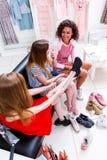 Υψηλός-γωνία που πυροβολείται των χαμογελώντας φίλων που επιλέγουν την τοποθέτηση στα αθλητικά παπούτσια που κάθονται στον πάγκο  Στοκ Εικόνες