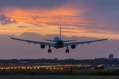 Υψηλός - ποιοτική εικόνα ενός αεροπλάνου που προσγειώνεται πριν από την ανατολή Στοκ Εικόνες