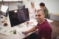 Υψηλό πορτρέτο γωνίας του χαμογελώντας επιχειρηματία που κρατά το κινητό τηλέφωνο στο γραφείο γραφείων Στοκ Φωτογραφίες