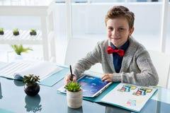 Υψηλό πορτρέτο γωνίας των εγγράφων ανάγνωσης επιχειρηματιών καθμένος στο γραφείο Στοκ Φωτογραφίες