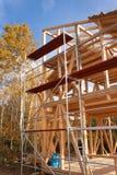 Υλικά σκαλωσιάς μετάλλων γύρω από το ατελές σπίτι Κατασκευή του οικολογικού σπιτιού Ξύλινο πλαίσιο του σπιτιού κάτω από την κατασ Στοκ Εικόνες