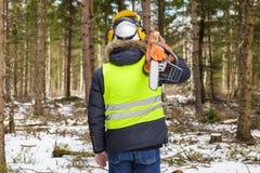 Υλοτόμος με το αλυσιδοπρίονο στον ώμο στο δάσος Στοκ Εικόνες