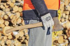 Υλοτόμος με το τσεκούρι και σχοινί κοντά στο σωρό των κούτσουρων Στοκ εικόνες με δικαίωμα ελεύθερης χρήσης