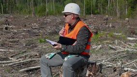 Υλοτόμος που γράφει και που σκέφτεται στο δάσος απόθεμα βίντεο