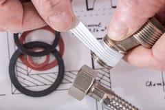 Υδραυλικός που βάζει μια τεφλόν ένωση σε ένα νήμα Στοκ Εικόνες
