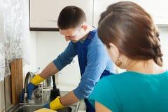 Υδραυλικός που επισκευάζει το νεροχύτη κουζινών για τη νοικοκυρά Στοκ Φωτογραφία