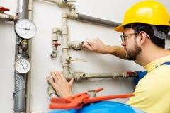 Υδραυλικός που κάνει τις εργασίες συντήρησης για τα συστήματα νερού και θέρμανσης στοκ φωτογραφίες