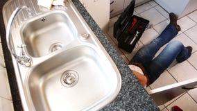 Υδραυλικός που καθορίζει το νεροχύτη σε μια κουζίνα απόθεμα βίντεο