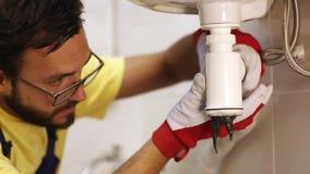 Υδραυλικός που καθορίζει το σιφώνιο νεροχυτών σε ένα λουτρό ή μια κουζίνα απόθεμα βίντεο