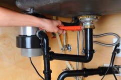 Υδραυλικός που χρησιμοποιεί το γαλλικό κλειδί κάτω από το νεροχύτη κουζινών Στοκ φωτογραφία με δικαίωμα ελεύθερης χρήσης