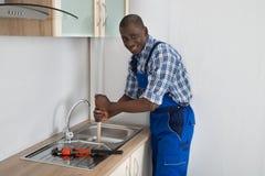 Υδραυλικός που χρησιμοποιεί το δύτη στο νεροχύτη κουζινών Στοκ εικόνα με δικαίωμα ελεύθερης χρήσης