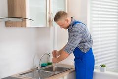 Υδραυλικός που χρησιμοποιεί το δύτη στο νεροχύτη Στοκ εικόνα με δικαίωμα ελεύθερης χρήσης