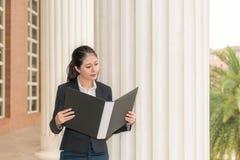 Φάκελλος και ανάγνωση εκμετάλλευσης δικηγόρων επιχειρηματιών Στοκ φωτογραφία με δικαίωμα ελεύθερης χρήσης