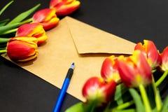Φάκελος ή επιστολή και τουλίπες στο μαύρο υπόβαθρο για το χαιρετισμό την ημέρα μητέρων ή γυναικών στοκ φωτογραφία