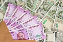 Φάκελος με ολοκαίνουργια ινδικά 2000 τραπεζογραμμάτια ρουπίων 500 τραπεζογραμμάτια ρουπίων στο υπόβαθρο