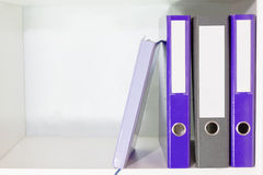 Φάκελλοι για τα έγγραφα και αρμόδιος για το σχεδιασμό σε ένα ράφι βιβλίων Στοκ Εικόνες