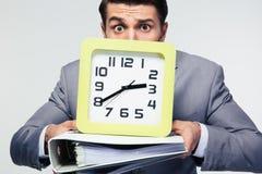 Φάκελλοι και ρολόι εκμετάλλευσης επιχειρηματιών Στοκ Φωτογραφία