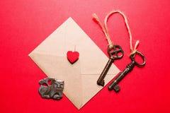 Φάκελος με καρδιά, δύο κλειδιά και λίγο τέρας σε ένα κόκκινο backgr Στοκ Εικόνες