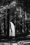 Φάντασμα που καλύπτεται με ένα άσπρο φύλλο φαντασμάτων σε μια αγροτική πορεία Κοκκώδης κατασκευασμένη εικόνα Στοκ Φωτογραφία