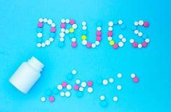 Φάρμακα επιγραφής από τις ταμπλέτες σε ένα μπλε υπόβαθρο στοκ εικόνα με δικαίωμα ελεύθερης χρήσης