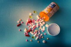 Φάρμακα θεραπείας μιγμάτων σωρών καψών χαπιών ταμπλετών, καταπραϋντικός, αντιβιοτικά, παυσίπονο πέρα από ένα μπλε άσπρο υπόβαθρο στοκ εικόνες