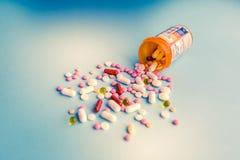 Φάρμακα θεραπείας μιγμάτων σωρών καψών χαπιών ταμπλετών, καταπραϋντικός, αντιβιοτικά, παυσίπονο πέρα από ένα μπλε άσπρο υπόβαθρο στοκ φωτογραφίες