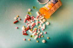 Φάρμακα θεραπείας μιγμάτων σωρών καψών χαπιών ταμπλετών, καταπραϋντικός, αντιβιοτικά, παυσίπονο πέρα από ένα μπλε άσπρο υπόβαθρο στοκ εικόνες με δικαίωμα ελεύθερης χρήσης
