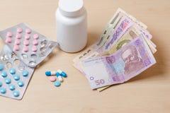 Φάρμακα, μπλε και ρόδινα χάπια και ουκρανικά χρήματα στον πίνακα στοκ φωτογραφία