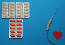 Φάρμακα στο μπλε υπόβαθρο για τη θεραπεία των καρδιακών παθήσεων, dropper τη βελόνα και τις ταμπλέτες του πορτοκαλιού και το κίτρ Στοκ Φωτογραφία