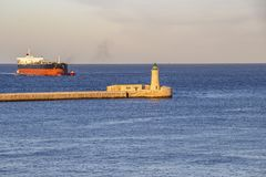 Φάρος κυματοθραυστών του ST Elmo με ένα σκάφος και tugboats εμπορευματοκιβωτίων, στο μεγάλο λιμάνι, Μάλτα στοκ φωτογραφίες με δικαίωμα ελεύθερης χρήσης