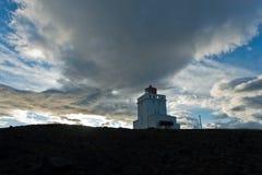 Φάρος στο βράχο Dyrholaey στο ηλιοβασίλεμα με το δραματικό ουρανό Στοκ φωτογραφία με δικαίωμα ελεύθερης χρήσης