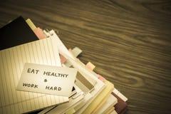 Φάτε την υγιή εργασία σκληρή  Ο σωρός των επιχειρησιακών εγγράφων σχετικά με το Des Στοκ φωτογραφία με δικαίωμα ελεύθερης χρήσης