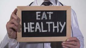 Φάτε την υγιή σύσταση διατροφής γραπτή σχετικά με τον πίνακα στα χέρια γιατρών διατροφής απόθεμα βίντεο