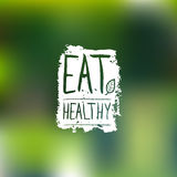 Φάτε το υγιές διανυσματικό λογότυπο με την εγγραφή χεριών Ετικέτα οργανικής τροφής στο υπόβαθρο θαμπάδων για το vegan καφέ, συσκε ελεύθερη απεικόνιση δικαιώματος