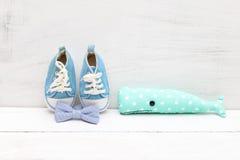 Φάλαινα παιχνιδιών, δεσμός τόξων και μπλε παπούτσια παιδιών ` s για ένα αγόρι σε ένα μόριο Στοκ φωτογραφίες με δικαίωμα ελεύθερης χρήσης