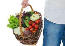 Φέρνοντας λαχανικά ατόμων σε ένα ψάθινο καλάθι Στοκ Εικόνες