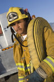 Φέρνοντας μάνικα πυρκαγιάς πυροσβεστών στον ώμο στοκ φωτογραφία με δικαίωμα ελεύθερης χρήσης