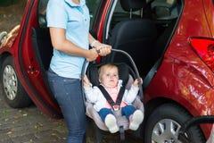 Φέρνοντας μωρό μητέρων στο κάθισμα αυτοκινήτων στοκ φωτογραφίες