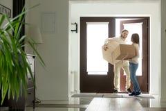 Φέρνοντας παράθυρα ζεύγους που μπαίνουν στο σπίτι, ιδιοκτήτες σπιτιού που κινείται στο νέο χ στοκ εικόνα με δικαίωμα ελεύθερης χρήσης