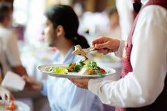 φέρνοντας σερβιτόρος πιάτ&om Στοκ Εικόνες