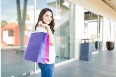 Φέρνοντας τσάντες εγγράφου ικανοποιημένων γυναικών στη λεωφόρο αγορών στοκ εικόνα